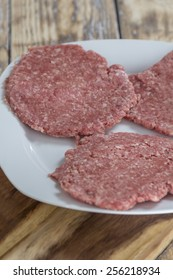 Three homemade hamburger patties on a plate on a rustic wooden table