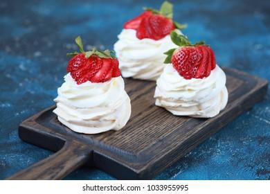 Three homemade mini cakes with meringue (pavlova) and cream cheese with strawberries. Selective focus.