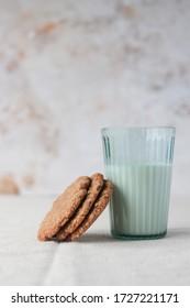 明るい田舎の背景に牛乳のグラスに寄りかかった3つの手作りのオートクッキー