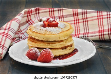 Three homemade pancakes with fresh strawberries and powdered sugar.  On a vintage wooden table with a red and whitetowel swirled behind plate.