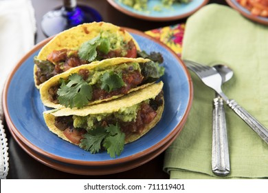 Three homemade spicy lentil tacos with guacamole, salsa and topped with cilantro