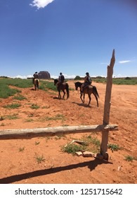 Three horseriders : two tourists guided by a Navajo tribesman in Monument VAlley Tribal Park - Arizona and Utah