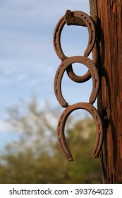 Three horseshoes hanging from a post