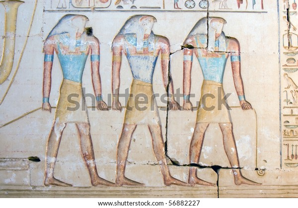 Three Horus Gods A trio of images of the ancient egyptian god Horus, depicted with the head of a falcon.  Hieroglyphic painted carving on a wall at the temple to Ramses II at Abydos, Egypt.