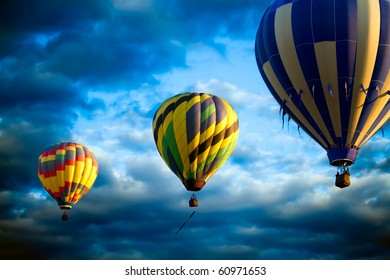 Three hot air balloons  lift off at sunrise, sunset  drifting on air currents. Flying before a dramatic background of clouds and bright blue sky.  Original illustration.