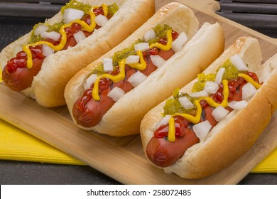 Three Hot Dogs with Mustard, Ketchup, pickle relish and onions