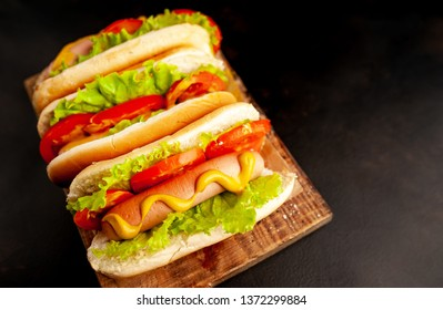 three hot dogs on a cutting board against a background of stone