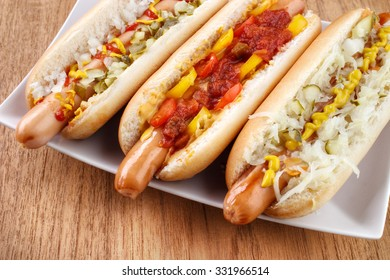 Three hot dogs on dish closeup , left with mustard , ketchup , onion and relish , middle with chili , salsa and small tomatoes, right with sauerkraut