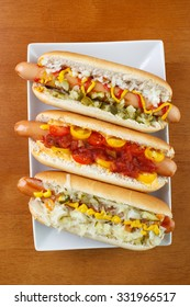 Three hot dogs on square plate , with mustard , ketchup , onion and relish , with chili , salsa and small tomatoes, and with sauerkraut , top view