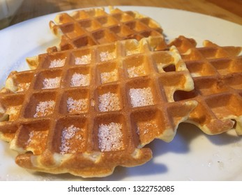 Three hot wafles with white sugar.