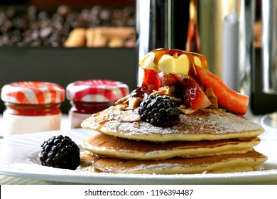 Three hotcakes with blackberry, strawberries, butter, walnut in pieces and honey.