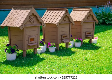 Three houses for bees on a green lawn.
