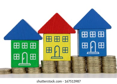 Three houses on rising column's of gold colored coins.