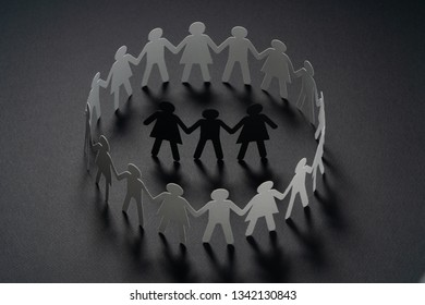 Three human paper figures surrounded by circle of paper people holding hands on dark surface. Bulling, conflict, segregation concept.