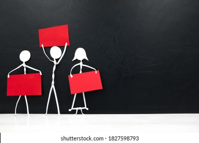 Three human stick figure holding red blank placards in black background. Activism, protest, demonstration, social movement and freedom of expression concept.