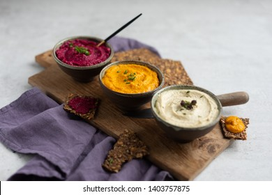 Three hummus dips, beet hummus, sweet potato or carrot or pumpkin hummus and parsnip hummus served with flax seeds crackers on a rustic wooden board with a purple napkin on a light natural stone table