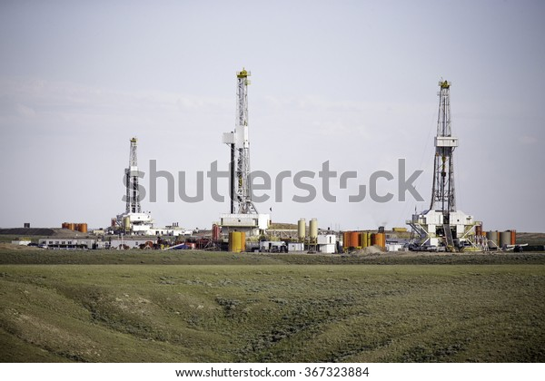 Three hydro-fracking derricks sitting on a plain.