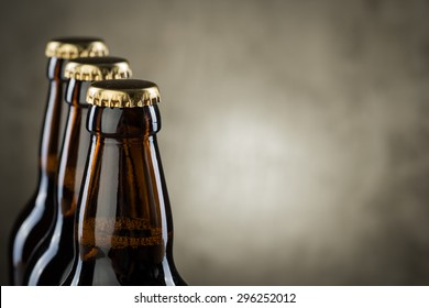Three ice cold beer bottles in a row over the grey concrete wall background