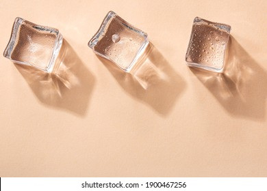 Three Ice cubes on pastel peach color background. Concept art. Minimal surrealism. Flat lay with copy space. Soft focus.