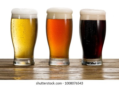 Three iced glasses of beer on the wooden table.  File contains clipping path.