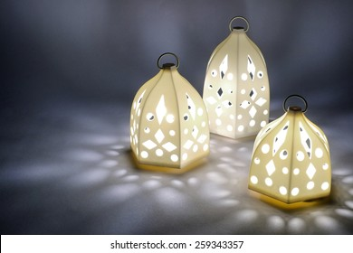 three illuminated arabic lantern on grey background arabic lantern