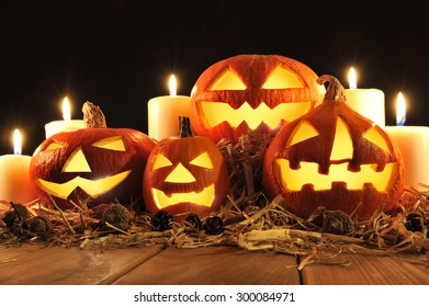 three illuminated halloween pumpkins and straw on old weathered wooden board in front of redbrown background in red light