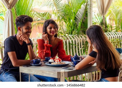 three indian beat Friends eating Sweets pancakes with masala tea in summer tropical beach cafe