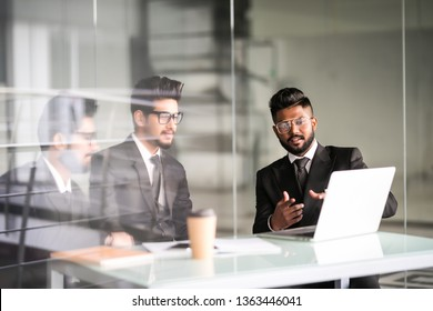 Three indian businessmen working together talking collaborate on laptop in office. Three Male business team discuss online project presentation corporate strategy with computer at meeting use laptop