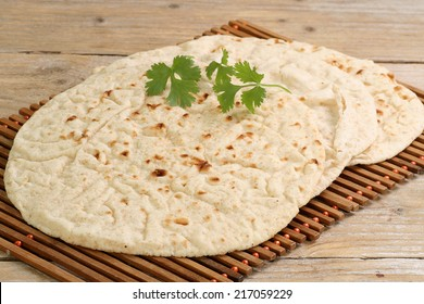Three indian chapattis with coriander garnish