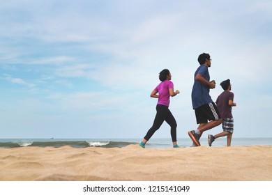 Three Indian friends doing a morning run along the beach by the ocean. Gokarna, India, December 2, 2017.