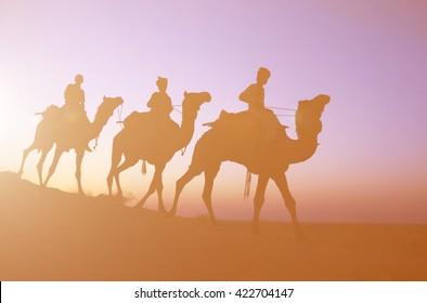 Three indigenous men riding camel through the dimly lit desert.