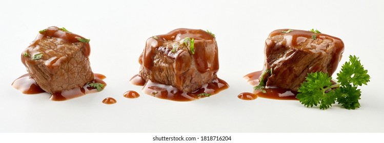 Three individual cubes of beef goulash in gravy sprinkled with fresh chopped parsley isolated on white in a panorama banner