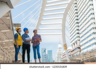 Three industrial engineer standing and looking to right side wear safety helmet with holding inspection and digital tablet on building outside. Engineering tools and construction concept.