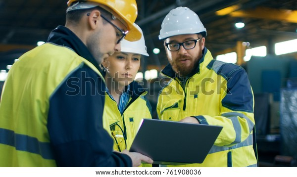 Three Industrial Engineers Talk with Factory Worker while Using Laptop. They Work at the Heavy Industry Manufacturing Facility.