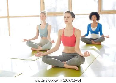Three intercultural girls keeping balance while sitting on mats in pose of lotus during yoga practice