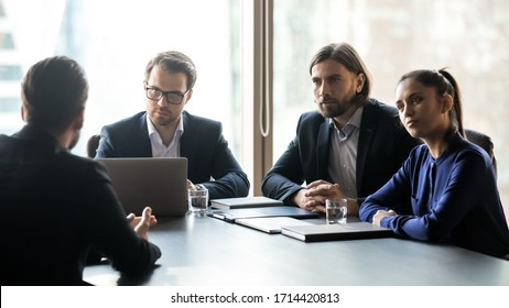 Three interested attentive hr managers listening to candidate on interview, sitting at table in boardroom, applicant seeker answering recruiters questions, colleagues looking at mentor coach