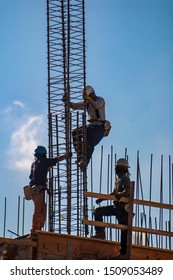 Three Iron Workers with one climbing up iron rebar against blue sky backdrop