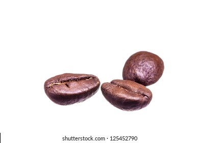three isolated coffee beans on white background with a shallow DOF