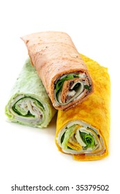Three isolated multicolored tortilla wraps with meat and vegetables
