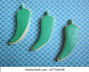 Three jalapeno-shaped sugar cookies with green icing