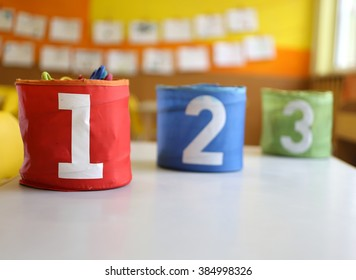 Three jars colored Red Green and blue with written one two and three in the kindergarten classroom