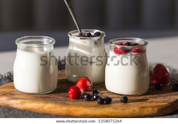 Three jars with natural homemade yogurt (neutral, with blueberries and apricot jam, with frozen strawberries)  with berries on wooden board.