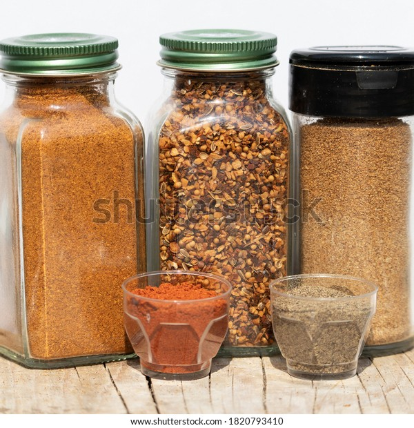 Three jars with spices of different grinding and two small bowls with red and black ground pepper