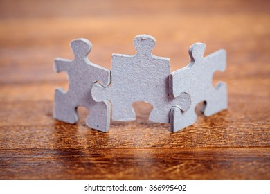 Three jigsaw puzzle pieces on a table joint together. Shallow depth of field