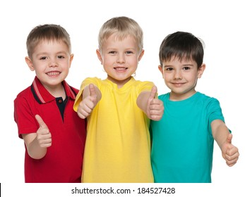 Three joyful boys are standing together on the white background and hold their thumbs up