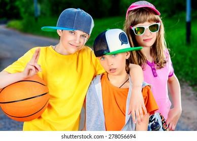 Three joyful children in the park. Active lifestyle. Summer.