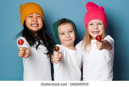 Three joyful friends kids in white t-shirts and colorful hats hold sweet lollipop candies happy smiling hugging together on blue mint background