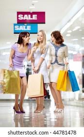 Three joyful girlfriends in shop with a credit card