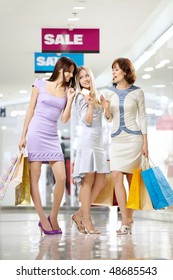 Three joyful girlfriends in shop with a credit card and bags