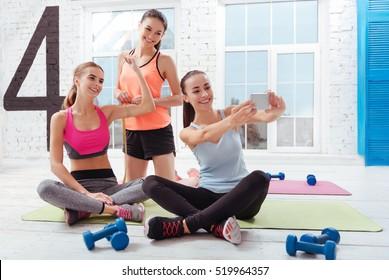Three joyful women making selfie after training